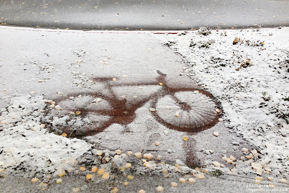 a bicycle leaves its mark in early snow on a sidewalk