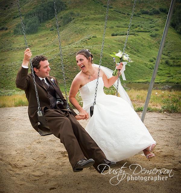 Wedding couple swinging at the playground