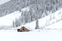 An old wooden barn offers shelter from a mountain snow storm