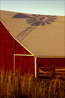 colorado stock photography - windmill shadow on red barn
