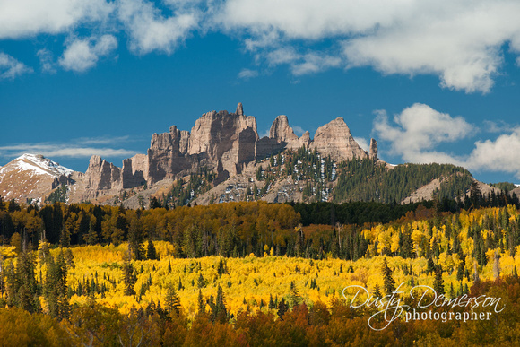 The Castles rock formations in the West Elk Wilderness Area of Colorado surrounded by an aspen forest in peak fall color.