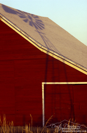 colorado stock photography - red barn and windmill shadow